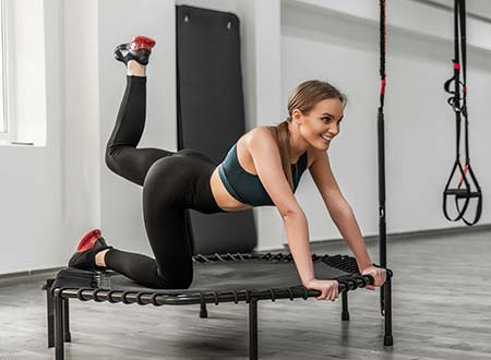 Lady working out on a folding fitness trampoline