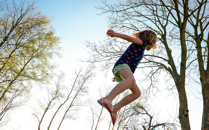 Girl in shorts jumping on a trampoline