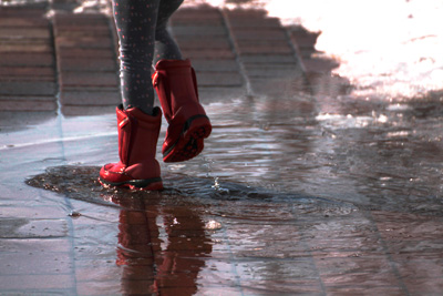 Girl walking in puddle of water